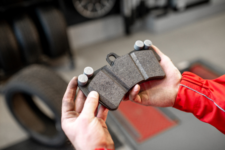 Auto mechanic holding new brake pad at the car service, close-up view