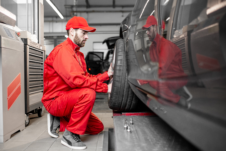 Two car service workers in red uniform changing wheel of a sport car at the tire mounting service