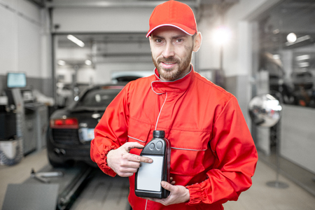 Portrait of a handsome auto mechanic in red uniform holding bottle with engine oil at the car service Foto de archivo - 114132917