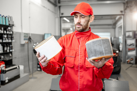 Auto mechanic in red uniform holding new and used air filter standing at the car service