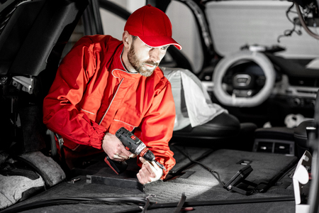 Handsome auto service worker in red uniform disassembling new car interior making some improvements