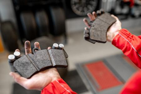 Mécanicien automobile tenant des plaquettes de frein neuves et usagées au service automobile, vue rapprochée