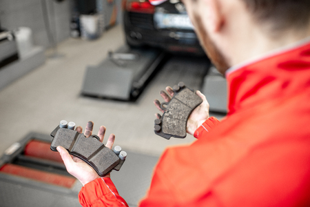 Auto mechanic holding new and used brake pads at the car service, close-up view