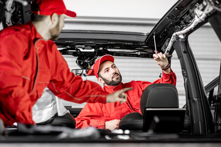 Two auto service workers in red uniform disassembling new car interior making some improvements indoors Stock Photo