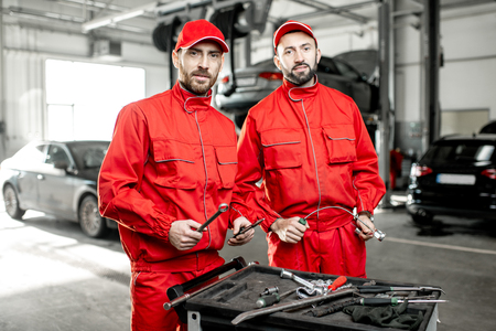 Portrait of a two handsome auto mechanics in red uniform standing with working tools at the car service