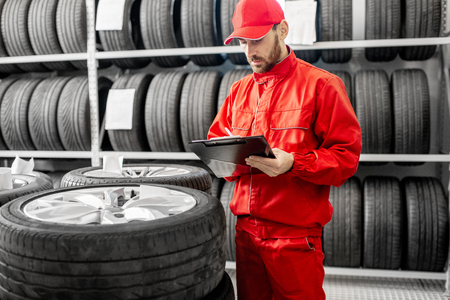 Worker or salesman in red uniform filling some documents checking goods in the warehouse with car tires