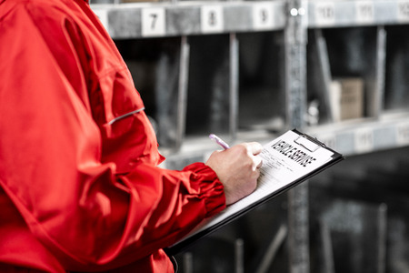 Worker filling some documents in the warehouse, close-up view