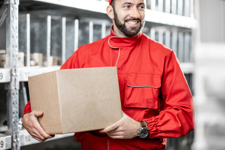 Worker in red uniform holding package in the warehouse, close-up view Stok Fotoğraf