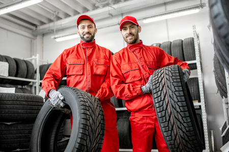 Portrait of a two workers in red uniform with car tires at the warehouse of the car service