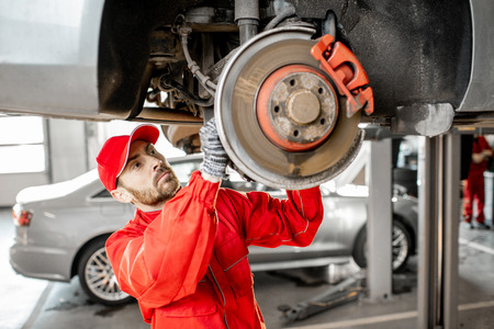 Auto mechanic in red uniform diagnosing car on the hoist at the car service