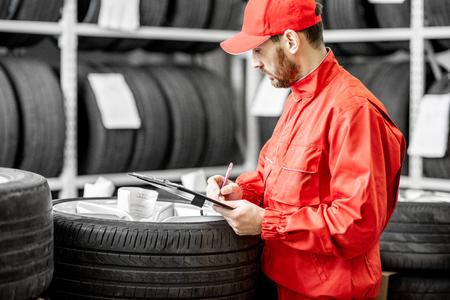Arbeiter oder Verkäufer in roter Uniform, die einige Dokumente ausfüllen, die Waren im Lager mit Autoreifen überprüfen