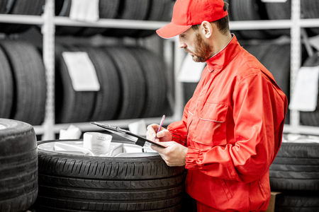 Worker or salesman in red uniform filling some documents checking goods in the warehouse with car tires Banco de Imagens - 114133682