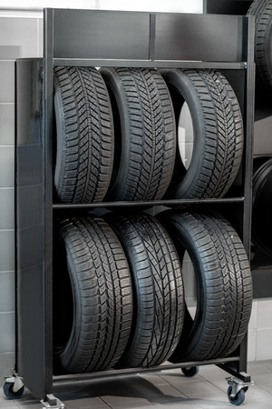 Car tires on the shelves at the wheel mounting service indoors Stok Fotoğraf