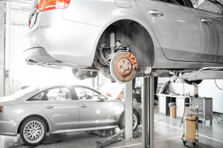 Samochód stojący na podnośniku podczas diagnostyki w serwisie samochodowym Zdjęcie Seryjne