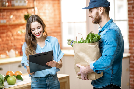Kurierdienstmitarbeiter, die einer glücklichen Kundin frische Lebensmittel liefern, die zu Hause einige Dokumente in der Küche unterschreibt