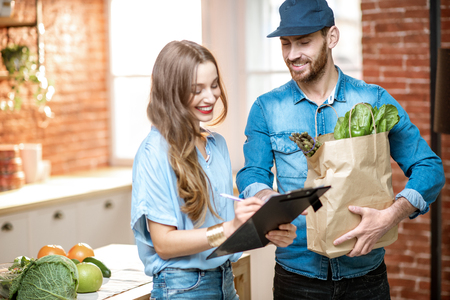 Trabajador de servicio de mensajería entregando alimentos frescos a una mujer feliz cliente firmando algunos documentos en la cocina de casa Foto de archivo