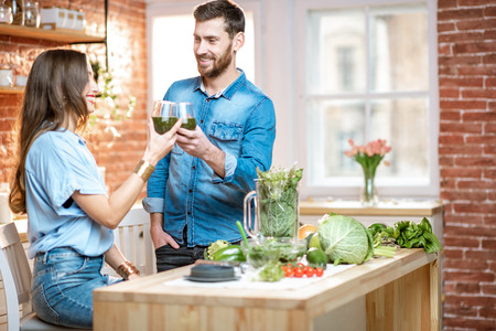 Young couple of vegetarians drinking fresh smoothie on the kitchen with green healthy food at home
