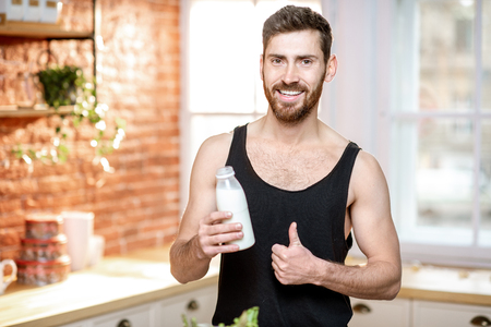 Portrait of a handsome sports man in black t-shirt drinking milk shake on the kitchen at home
