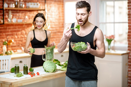 Young sports couple having snack with healthy salad and green smoothie on the kitchen at home Stockfoto