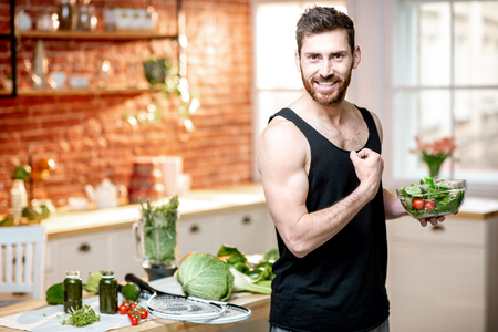 Portrait of a handsome sports man showing muscles, eating healthy vegetarian salad on the kitchen at home Stockfoto