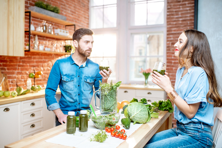Young couple of vegetarians drinking smoothie at the table full of fresh green products on the kitchen at home Stock Photo