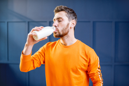 Conceptual portrait of a sports man in bright sweater drinking milk from the bottle on the blue background Stock Photo - 114134391