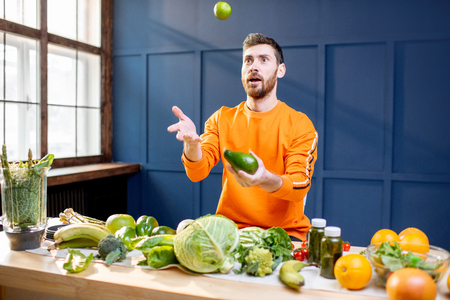 Conceptual portrait of a vegetarian man in bright sweater throwing up vegetables on the blue background