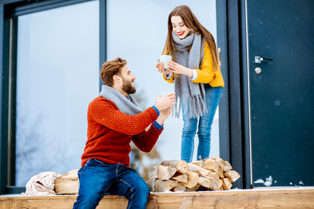 Young couple dressed in colorful sweaters enjoying hot drinks on the terrace of the modern house in the mountains during the winter