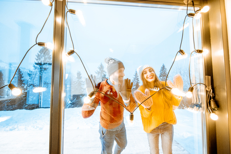 Young couple in bright sweaters and hats standing on the terrace of the house in the mountains during the winter time, view through the window with garland Stock Photo