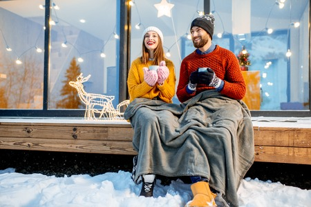 Young couple warming up with plaid and hot drinks sitting on the terrace of the modern house in the mountains durnig the winter holidays Stockfoto