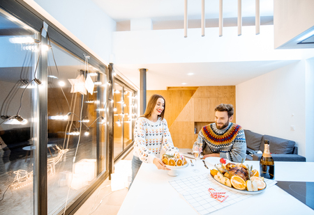 Young couple having festive dinner sitting together in the modern house during the winter holidays. Wide interior view Stock Photo