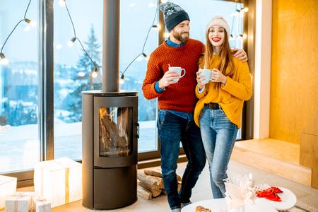 Junges Paar in hellen Pullovern und Hüten, die zusammen mit heißen Getränken am Kamin im modernen Haus während der Winterzeit stehen
