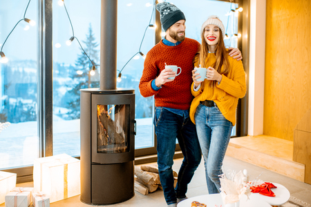 Young couple dressed in bright sweaters and hats standing together with hot drinks near the fireplace in the modern house durnig winter time