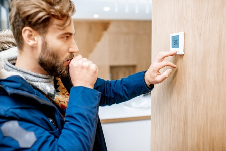 Man in winter clothes feeling cold adjusting room temperature with electronic thermostat at home Stok Fotoğraf - 114135515