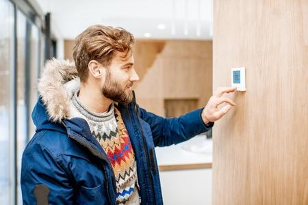 Hombre en ropa de invierno sintiendo frío ajustando la temperatura ambiente con termostato electrónico en casa Foto de archivo