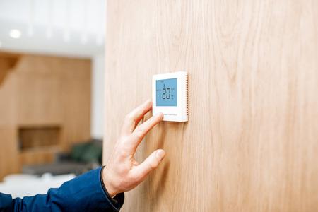 Regulacja temperatury w pomieszczeniu za pomocą termostatu elektronicznego w domu, widok z bliska bez twarzy