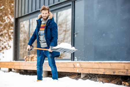 Handsome man in winter clothes cleaning snow with a shovel near the modern house in the mountains Stock Photo