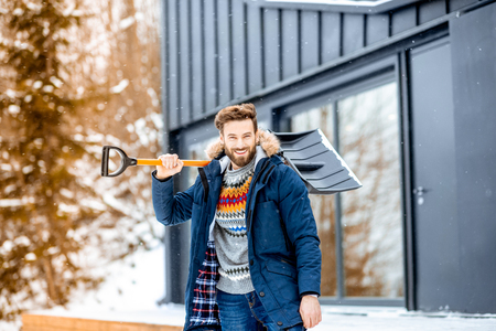 Portrait of a man in winter clothes with a snow shovel near the modern house in the mountains Stock Photo