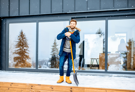 Portrait of a man in winter clothes standing with snow shovel on the terrace of the building in the mountains