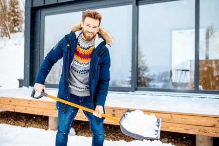 Handsome man in winter clothes cleaning snow with a shovel near the modern house in the mountains Standard-Bild
