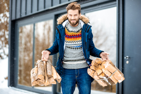 Handsome man in winter clothes carrying firewoods on the terrace near the modern house in the mountains