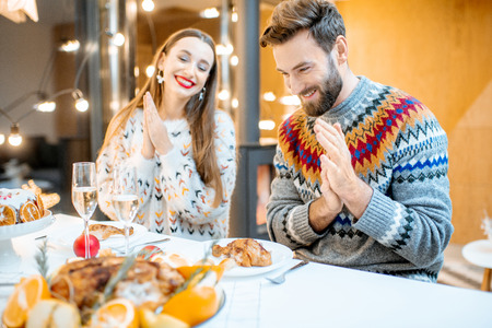 Young couple having festive dinner sitting together in the modern house during the winter holidays