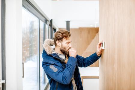 Hombre en ropa de invierno sintiendo frío ajustando la temperatura ambiente con termostato electrónico en casa