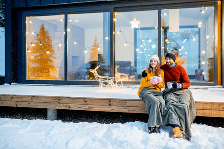 Young couple warming up with plaid and hot drinks sitting on the terrace of the modern house in the mountains durnig the winter holidays Stock Photo