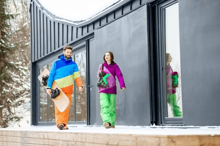 Young couple in colorful ski suits walking together with snowboard near the modern house or hotel in the mountains