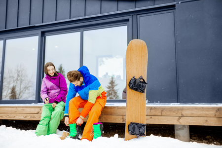 Young couple in ski suits preparing for snowboarding sitting on the terrace of the modern house in the mountains Stock Photo