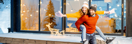 Young couple dressed in bright sweaters and hats having fun together near the decorated house during the winter holidays