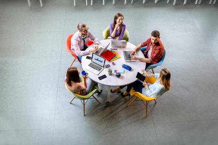 Zespół młodych współpracowników ubranych niedbale pracujących razem z laptopami siedzącymi przy okrągłym stole w biurze, widok z góry
