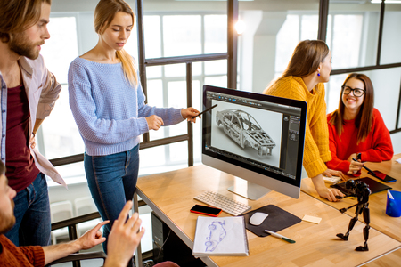 Grupo de jóvenes compañeros de trabajo creativos que diseñan un modelo de automóvil en el lugar de trabajo con computadoras en el interior de la oficina moderna