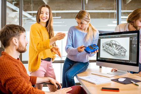 Groupe de jeunes collègues créatifs concevant un modèle de voiture sur le lieu de travail avec des ordinateurs à l'intérieur du bureau moderne